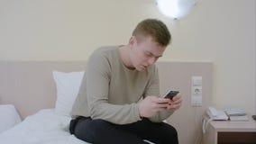 Homem novo preocupado que datilografa uma mensagem dos sms em seu telefone celular que senta-se na cama em casa Foto de Stock