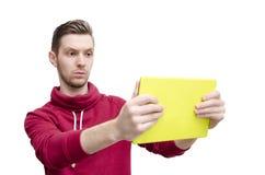 Homem novo puro sério que guarda e que olha a tabuleta Fotografia de Stock Royalty Free