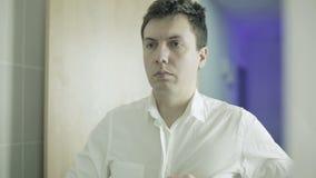 Homem novo que abotoa os botões de camisa brancos vídeos de arquivo