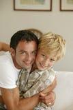 Homem novo que abraça o rapaz pequeno Fotos de Stock