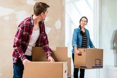 Homem novo que abre uma caixa ao mover-se com sua amiga na Imagens de Stock