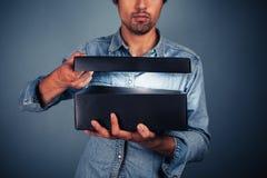 Homem novo que abre uma caixa emocionante Fotografia de Stock