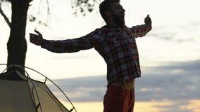Homem novo que acorda na barraca, esticando as mãos e bocejando, feriados de acampamento vídeos de arquivo