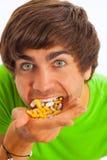 Homem novo que alimenta-se comprimidos Fotografia de Stock Royalty Free
