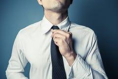 Homem novo que amarra o seu laço Foto de Stock