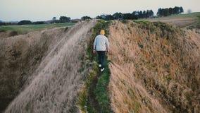Homem novo que anda ao longo do trajeto íngreme estreito perigoso sobre um penhasco do por do sol, mulher do turista da vista tra filme