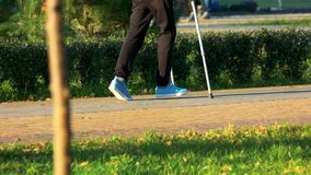 Homem novo que anda com as muletas no parque fotografia de stock royalty free