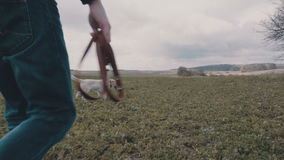 Homem novo que anda com seu Labrador amarelo através do campo video estoque