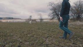 Homem novo que anda com seu Labrador amarelo através do campo vídeos de arquivo