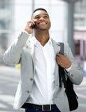 Homem novo que anda e que fala no telefone celular Fotografia de Stock Royalty Free