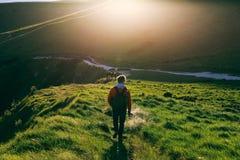 Homem novo que anda em um trajeto ao lado da costa jurássico durante o por do sol Imagem de Stock Royalty Free