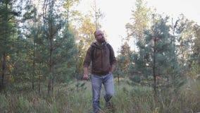 Homem novo que anda na floresta do outono, caminhando na floresta filme