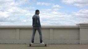 Homem novo que aparece no quadro e que monta um skate no dia nebuloso video estoque