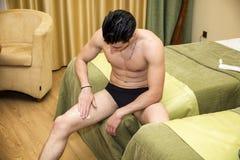 Homem novo que aplica a loção do corpo aos pés Foto de Stock