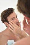 Homem novo que aplica o creme facial foto de stock royalty free