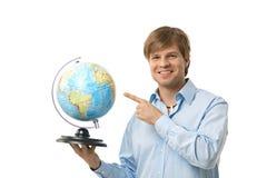 Homem novo que aponta ao globo Fotografia de Stock Royalty Free