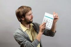 Homem novo que aponta a data no calendário Foto de Stock