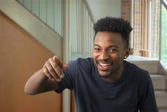 Homem novo que aponta o dedo e que ri alguém escola foto de stock royalty free