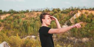 Homem novo que aponta o sentido com seu dedo ao caminhar nas montanhas, foto horizontal imagem de stock