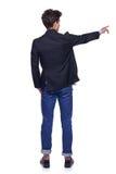 Homem novo que aponta, vista traseira Fotografia de Stock