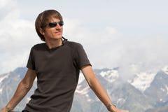Homem novo que aprecia as montanhas Fotografia de Stock Royalty Free
