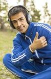 Homem novo que aprecia a escuta a música na tabuleta Imagem de Stock
