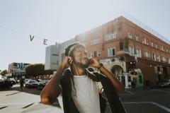 Homem novo que aprecia a música ao andar nas ruas fotos de stock royalty free