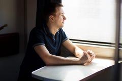 Homem novo que aprecia o curso do trem - deixando seu carro em casa, olha fora da janela, tem o tempo para admirar a paisagem fotografia de stock royalty free