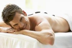 Homem novo que aprecia o tratamento de pedra quente Fotografia de Stock Royalty Free