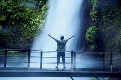 Homem novo que aprecia a opinião da cachoeira de Situ Gunung imagem de stock