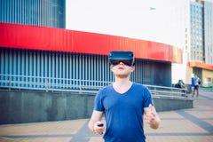 Homem novo que apreciam auriculares dos vidros da realidade virtual ou espetáculos 3d que estão contra o fundo moderno da constru Imagem de Stock