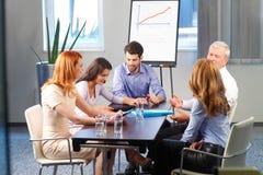 Homem novo que apresenta ideias a sua equipe do negócio Imagem de Stock