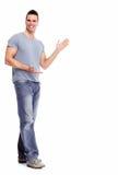 Homem novo que apresenta um copyspace. Fotografia de Stock