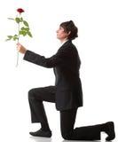 Homem novo que apresenta uma flor - o vermelho levantou-se   Fotos de Stock Royalty Free
