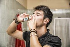 Homem novo que aspira o pulverizador de nariz no banheiro Imagens de Stock Royalty Free