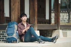 Homem novo que backpacking em Coreia assento em uma casa tradicional coreana e utilização de um tablet pc fotos de stock royalty free