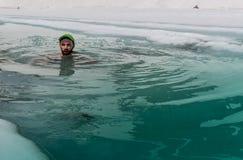Homem novo que banha-se no furo do gelo Fotografia de Stock