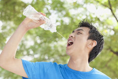 Homem novo que bebe a água engarrafada no parque Imagens de Stock