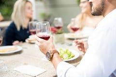 Homem novo que bebe algum vinho com amigos imagens de stock