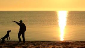 Homem novo que bebe do thermocup em uma praia filme