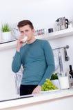 Homem novo que bebe um vidro do leite na cozinha imagem de stock