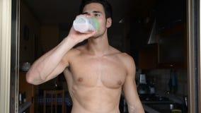Homem novo que bebe uma bebida do batido ou uma agitação da proteína vídeos de arquivo
