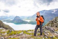 Homem novo que caminha em Besseggen O indivíduo feliz aprecia o lago bonito e o bom tempo em Noruega Fotografia de Stock