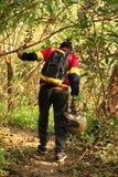 Homem novo que caminha na selva tropical com trouxa Caminhante masculino com mochila que anda ao longo da fuga da floresta Imagens de Stock Royalty Free