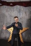 Homem novo que canta com microfone Fotos de Stock Royalty Free