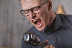 Homem novo que canta com microfone Foto de Stock Royalty Free