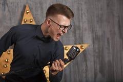 Homem novo que canta com microfone Imagens de Stock Royalty Free
