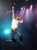 Homem novo que canta e que salta na fase Foto de Stock Royalty Free