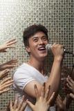 Homem novo que canta em um microfone com lotes das mãos que alcançam para ele Imagem de Stock Royalty Free