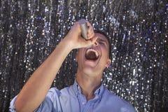 Homem novo que canta em um microfone no karaoke Imagem de Stock Royalty Free